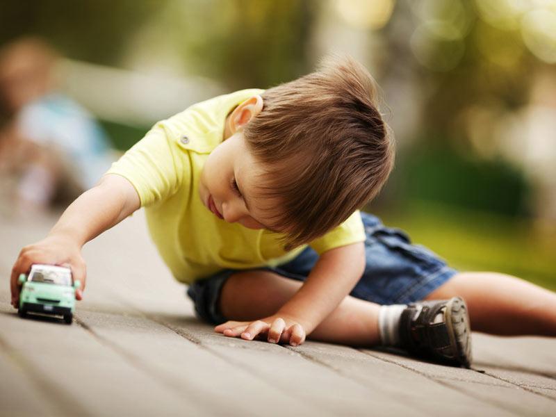 پسربچه در حال بازی با ماشین